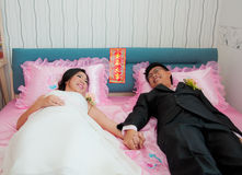 Bride and groom hold their hand and lay on the bed Royalty Free Stock Image