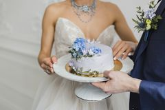 Bride and groom hold wedding cake Royalty Free Stock Photography