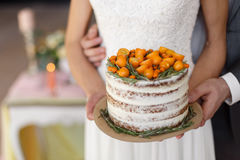 The bride and groom hold a wedding cake decorated with orange berries on the table background. Focus on the cake,. Close-up. Horizontal photo Stock Images