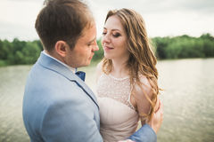 Bride and groom holding beautiful wedding bouquet. Lake, forest Stock Images