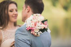 Bride and groom holding beautiful wedding bouquet. Lake, forest Stock Image