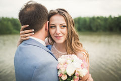 Bride and groom holding beautiful wedding bouquet. Lake, forest Royalty Free Stock Photography