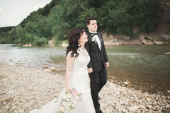 Bride and groom holding beautiful wedding bouquet. Posing near river Royalty Free Stock Image