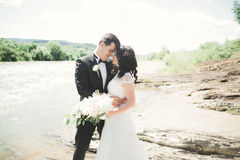 Bride and groom holding beautiful wedding bouquet. Posing near river Stock Images