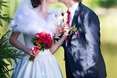 Bride and groom holding beautifully decorated wedding glasses wi Stock Photos
