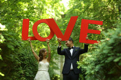Bride and groom holding big LOVE letters Stock Photo