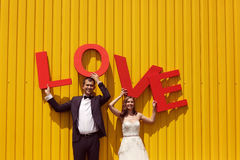 Bride and groom holding big LOVE letters Royalty Free Stock Photography