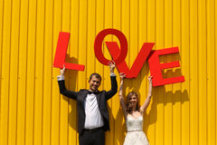 Bride and groom holding big LOVE letters Stock Photos