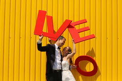 Bride and groom holding big LOVE letters Royalty Free Stock Images