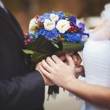 The bride and groom are holding a bouquet of flowers. royalty free stock photography