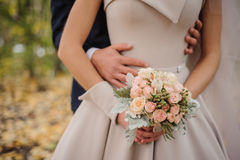 Bride and groom holding bouquet Stock Photos