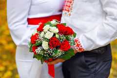 Bride and groom holding a bouquet of red wedding Stock Photos