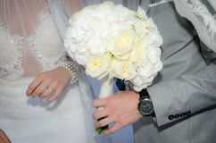 Bride and groom holding bouquet of roses Royalty Free Stock Photography