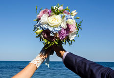 Bride and groom holding bouquet of roses on seaside background. Royalty Free Stock Photography
