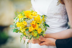 Bride and groom holding a bouquet of sunflowers. Royalty Free Stock Images