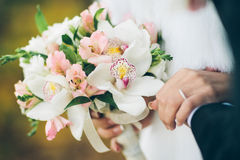 A bride and groom holding a bouquet of white and pink flowers Stock Photo