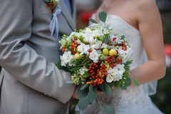 Bride and groom holding bridal bouquet Stock Photos