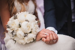 Bride and groom holding bridal bouquet Royalty Free Stock Photos