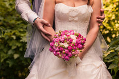 Bride and groom holding bridal bouquet close up Stock Image
