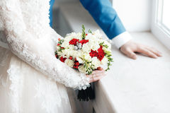Bride and groom holding bridal bouquet close up. red and white roses, freesia, brunia decorated in composition Stock Photo