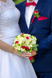 Bride and groom holding colorful flowers bouquet with hands on w Stock Photo