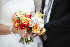 Bride and groom holding colourful wedding bouquet. Marriage concept Royalty Free Stock Image