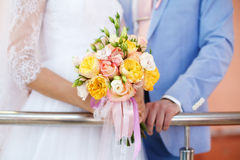 Bride and groom holding colourful wedding bouquet. Marriage concept Stock Image
