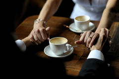 Bride and groom holding each other's hands. While sitting at the table Stock Image