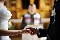 Bride and groom holding each other's hands. Bride and groom are holding each other's hands during church wedding ceremony Royalty Free Stock Photos