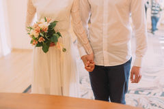 Bride and groom holding each other's hands with rings at wedding ceremony Stock Image