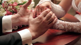 Bride and groom holding each other's hands at the table stock video footage