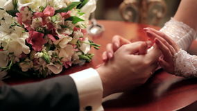 Bride and groom holding each other's hands at the table stock footage