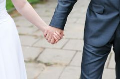 Bride and groom holding each others hands Stock Photos