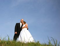 Bride & Groom Holding Embracing on Grassy Hill. This lovely photo is a bride and groom embracing each other on a grassy hill against bright blue sky Stock Photography