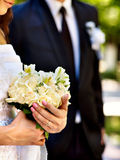 Bride and groom holding flower outdoor. Royalty Free Stock Photography