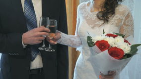 The bride and groom holding glasses of champagne. In front of him and clink their glasses stock video