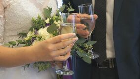 Bride and groom holding glasses of wine. Close-up. Bride and groom holding glasses of champagne in front of him and clink their glasses. Close-up stock video