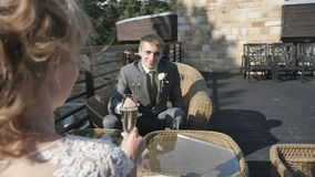 Bride and groom holding glasses of champagne sitting on the veranda of summer cafe stock video footage