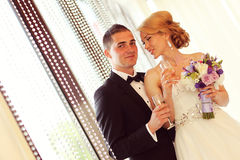 Bride and groom holding glasses of champagne. Sunny lovely day Stock Photos