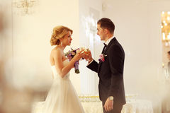 Bride and groom holding glasses of champagne. Sunny lovely day Stock Photo