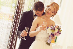 Bride and groom holding glasses of champagne. Sunny lovely day Royalty Free Stock Photo