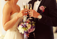 Bride and groom holding glasses of champagne. Sunny lovely day flowers bouquet Stock Images