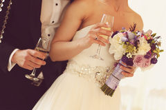 Bride and groom holding glasses of champagne. Sunny lovely day flowers bouquet Royalty Free Stock Image