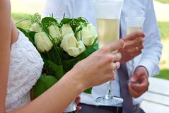 Bride and groom holding glasses and flowers Royalty Free Stock Image