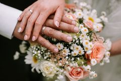 Bride and groom holding hand on the bouquet stock images