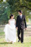 Bride and groom holding hand and walk in garden Royalty Free Stock Photo