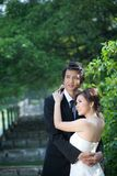Bride and groom holding hand and walk in garden Stock Photography