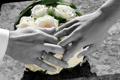 Bride and groom holding hands. Close up of bride and groom holding hands with bridal bouquet in the background Royalty Free Stock Photography