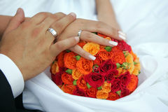 Bride and groom holding hands. Newlywed couple holding hands on wedding dress and bouquet Royalty Free Stock Photo