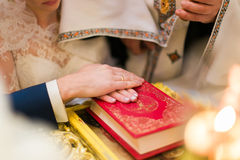 Bride and groom are holding hands on Bible Stock Photography